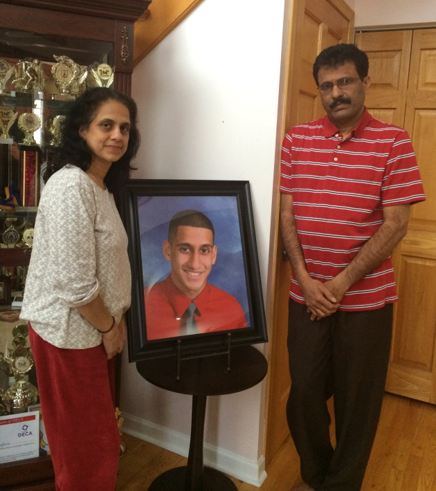 Parents Mathew and Lovely Varughese, standing next to a photo of their son Pravin Varughese. | PHOTO BY ALEX V. HERNANDEZ/STAFF REPORTER